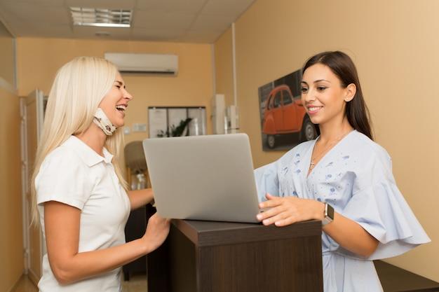 女性はレセプションで働いて、医者と話します