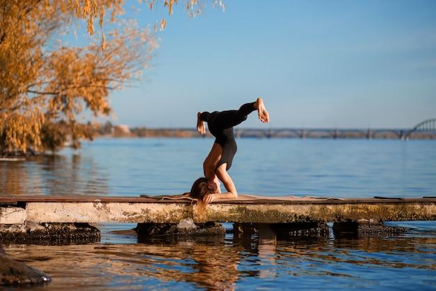 Тренировка йоги молодой женщины практикуя на тихой деревянной пристани с городом