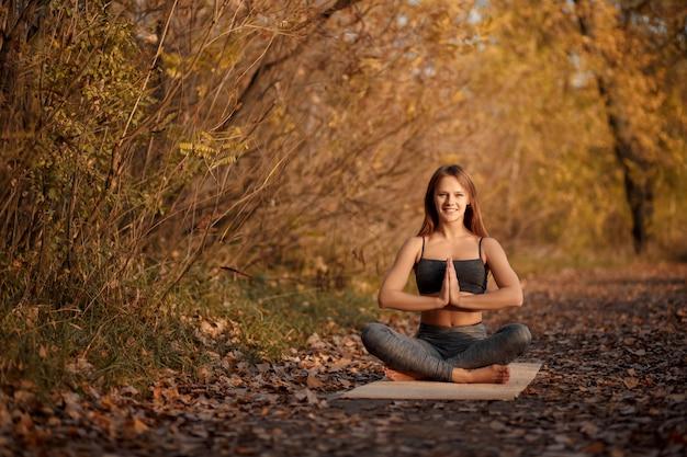 Тренировка йоги молодой женщины практикуя на парке осени с желтыми листьями