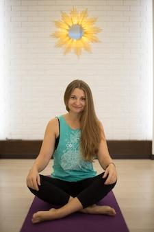 Шикарный тренер йоги женщины представляя в занятиях йогой