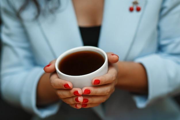 青いジャケットのトップビューの女性は一杯のコーヒーを保持します