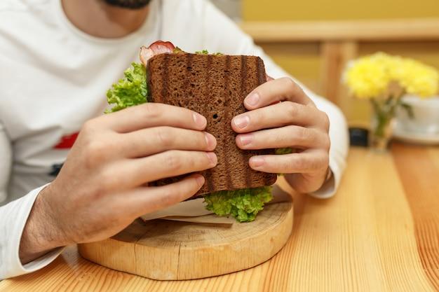 食欲をそそる空腹の若い男がサンドイッチを食べる