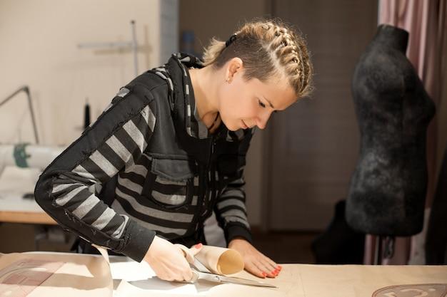 金髪の女性の裁縫師は服を作るためのクラフト型紙からカットします。