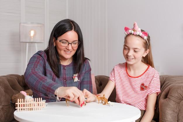 Мама и дочка проводят время вместе, сидят на диване, общаются и играют с игрушечными животными