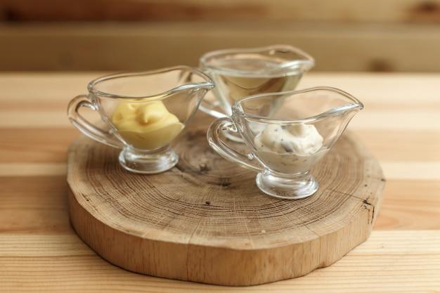 Набор из трех прозрачных соусников с разными соусами на деревянной тарелке