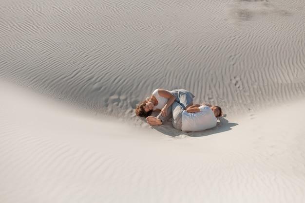 砂漠の白い砂の上に敷設するロマンチックなペア