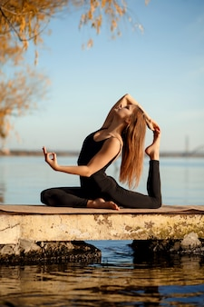 Молодая девушка практикующих йогу упражнения на тихой пристани в осенний парк