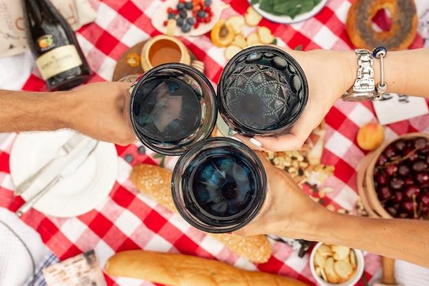 夏のピクニックの休日。トップビューの友人が市松模様の毛布にメガネをチャリンという音します。