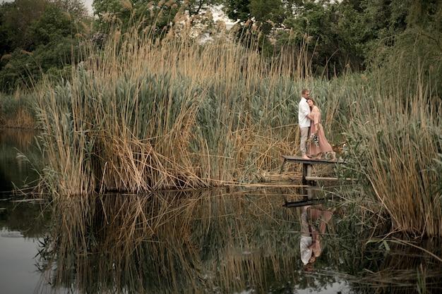 愛のカップルが抱擁し、自然に木製の桟橋でキスします。
