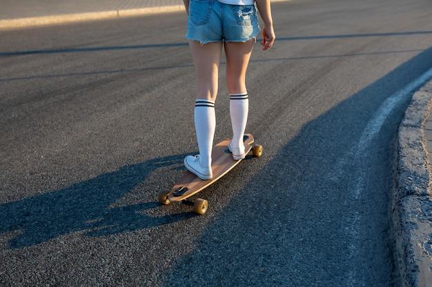 木製のロングボードに乗って白いストッキングで足をクローズアップ