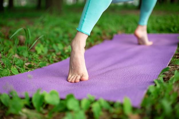 Тонкая брюнетка занимается спортом и выполняет позы йоги в летнем парке. женщина делает упражнения на коврик для йоги, ноги крупным планом