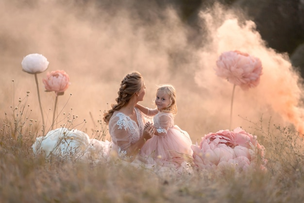 小さな女の子は、非現実的な大きなピンクの装飾花に囲まれたフィールドに座ってママを抱擁します。