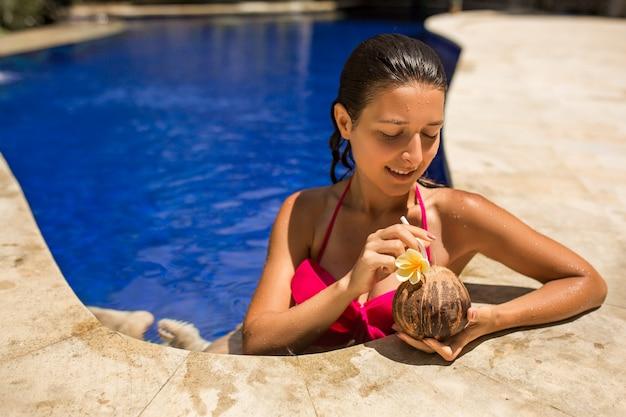 Сексуальная стройная брюнетка молодая самка позирует со свежим кокосом в бассейне с кристально голубой водой. королевский тропический курортный отдых.