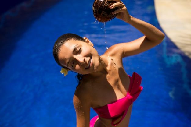 Сексуальная стройная брюнетка молодая самка поливает себя свежим кокосовым молоком в бассейне с кристально голубой водой. королевский тропический курортный отдых.
