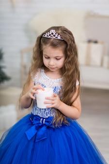 Милая маленькая девочка в пышном голубом платье держит искусственную свечу в руках для украшения дома на рождественские праздники. подходящий для детей пейзаж.