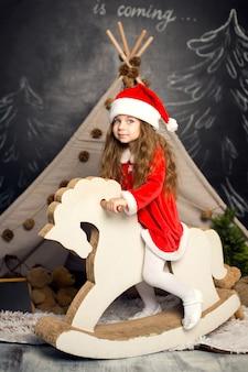 Маленькая девочка в костюме санта на лошадке-качалке готова отмечать праздники.