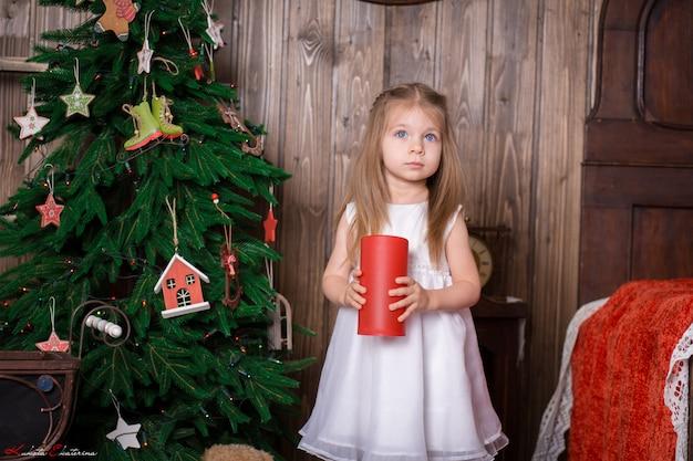 Маленькая девочка держит декоративную красную свечу, чтобы украсить комнату для рождественских праздников