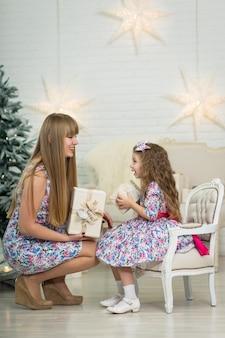 クリスマスツリーの近くのお母さんと一緒に大きなクリスマスプレゼントを持つ少女のポーズ