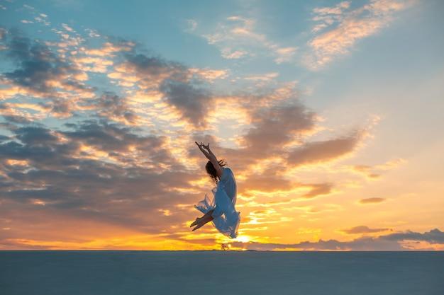 夕暮れ時の砂の砂漠で白いドレスを着た少女が踊りポーズをとる