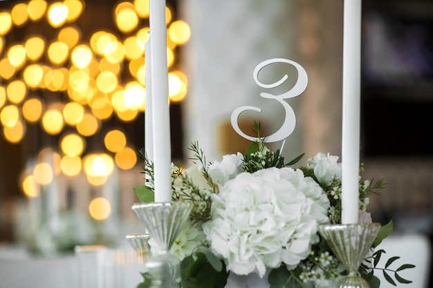 結婚式のテーブルセッティングは、生花と白いキャンドルで飾られています