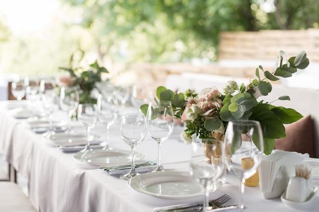 Сервировка свадебного стола украшена живыми цветами в латунной вазе.