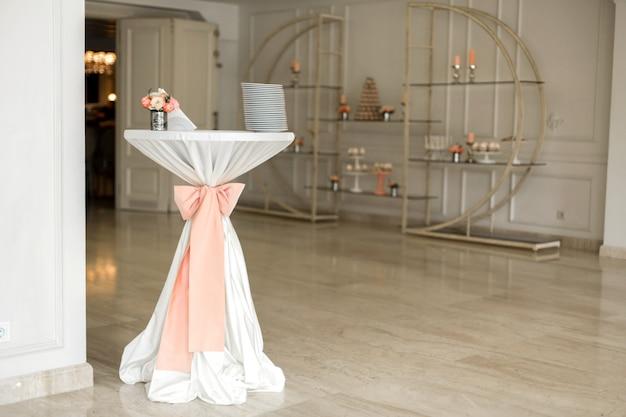 ピンクの布で飾られた結婚式のコンシェルジュテーブル。