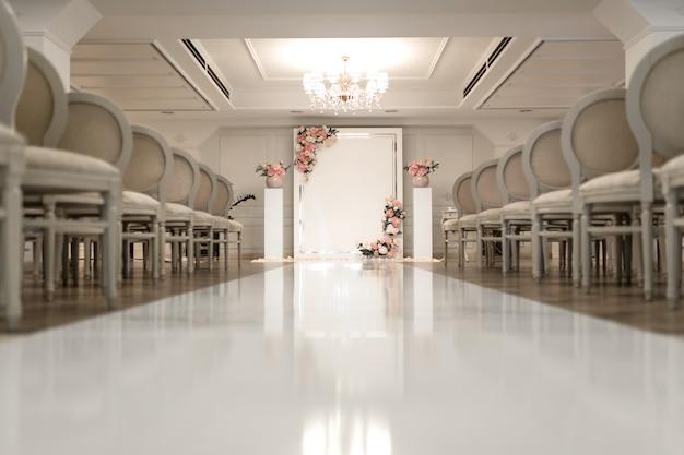 Свадебный зал. ряды белых праздничных стульев для гостей.