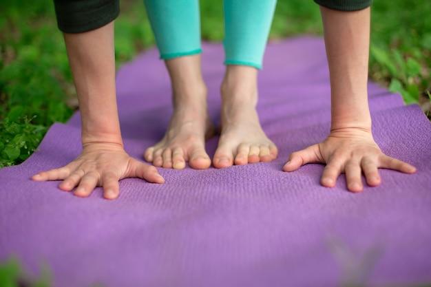 Тонкая брюнетка занимается спортом и выполняет позы йоги в летнем парке.