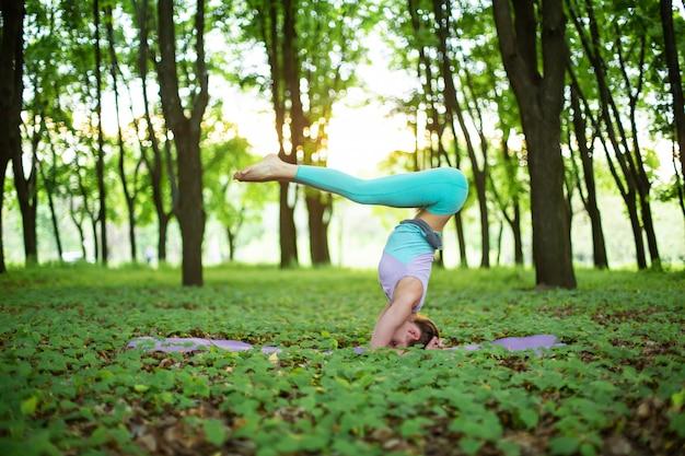 Худенькая брюнетка занимается спортом и выполняет позы йоги в летнем парке на закате