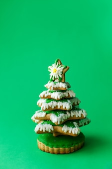 クリスマスの休日のお菓子。クリスマス休暇の伝統。緑の背景にクリスマスツリーのジンジャーブレッド。コピースペース休日の概念