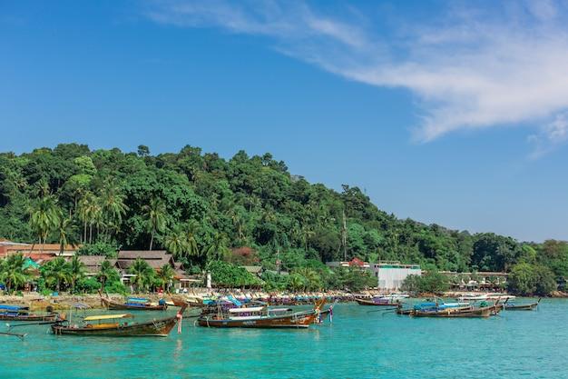 Традиционные тайские рыбацкие лодки, завернутые в цветные ленты. на фоне тропического острова.