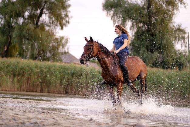 浅い湖で馬に乗る少女。馬は日没時に水の上を走ります。馬と一緒に気をつけて歩いてください。強さと美しさ