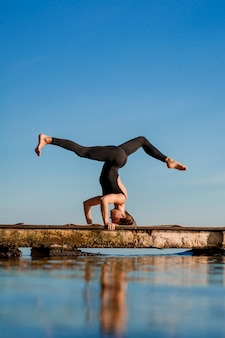 Тренировка йоги молодой женщины практикуя на тихой деревянной пристани с городом. спорт и отдых в суете города