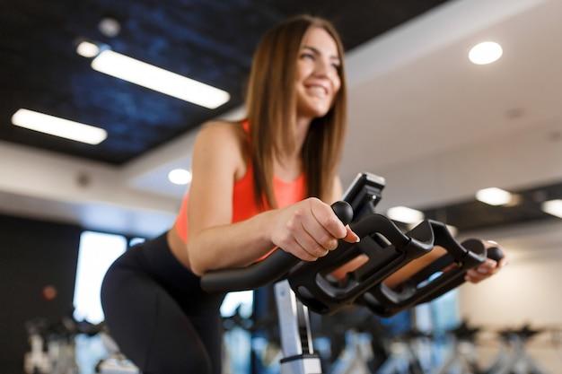 Портрет молодой стройной женщины в спортивной тренировки на велотренажере в тренажерном зале. спортивно-оздоровительный образ жизни