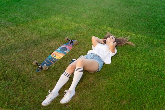 Молодая девушка наслаждается лежать на зеленой лужайке и слушать музыку после катания на доске