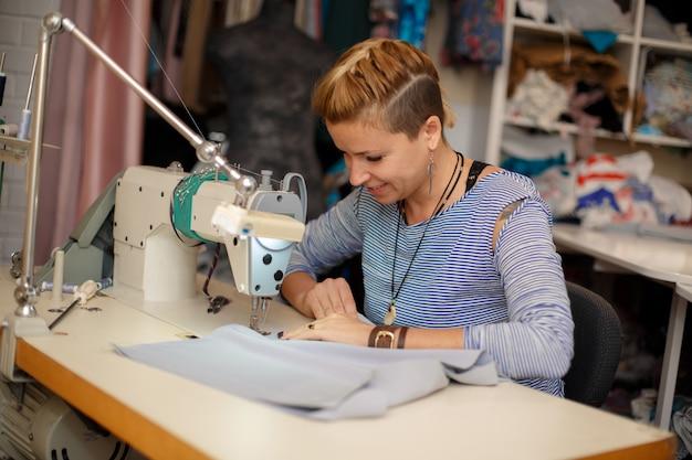 若い女性の金髪仕立て屋はミシンで動作します。ドレス製造業