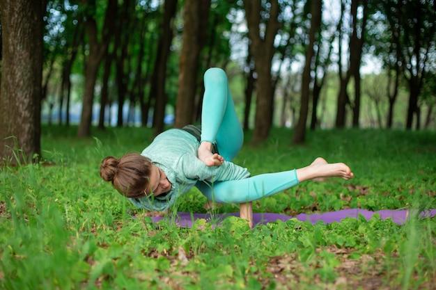 Худенькая брюнетка занимается спортом и выполняет красивые и сложные позы йоги в летнем парке. зеленый пышный лес. женщина делает упражнения на коврик для йоги