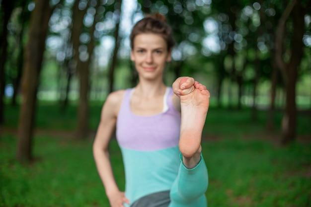 細いブルネットの少女はスポーツをし、夏の公園で美しく洗練されたヨガのポーズを実行します。の緑の森。ヨガマット、足前方クローズアップで演習を行う女性