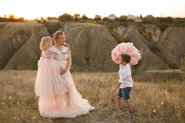 スタイリッシュな若い男の子は日没でフィールドで彼のお母さんに大きな花を与える