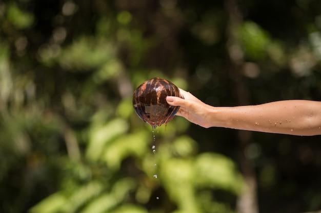 女性の手は水からココナッツを引き出した。ジャングルグリーン