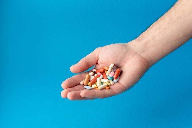 Горсть цветных таблеток на ладони. медицинский покупки в аптеке.