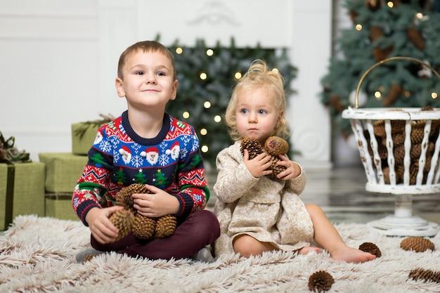 女の子と男の子のクリスマスツリーを飾るためにコーンと床で遊んで。クリスマスツリーとクリスマスプレゼントの箱の近くの兄と妹。メリークリスマスとハッピーホリデー