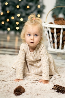 クリスマスツリーとクリスマスの前夜に新年の装飾の写真でブロンドの髪を持つ少女の肖像画