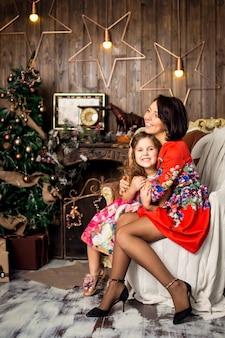 家族はクリスマスを祝います。魔法の夜の娘と一緒に幸せな母。母は娘を抱擁します。メリークリスマスとハッピーホリデー。優しさ、注意、相互理解。