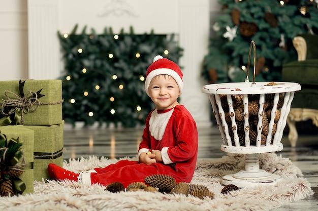 クリスマスツリーを飾るためにコーンで床で遊ぶかわいい幼児の肖像画。クリスマスツリーとクリスマスプレゼントの箱の近く。メリークリスマスと幸せな休日。
