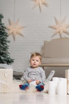 クリスマスツリーの近くの床で遊ぶかわいい幼児の肖像画。メリークリスマスと幸せな休日。