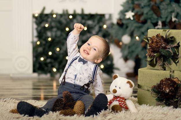 Портрет игры маленького мальчика с сосновыми шишками около рождественской елки. рождественские украшения. веселого рождества и счастливого нового года .