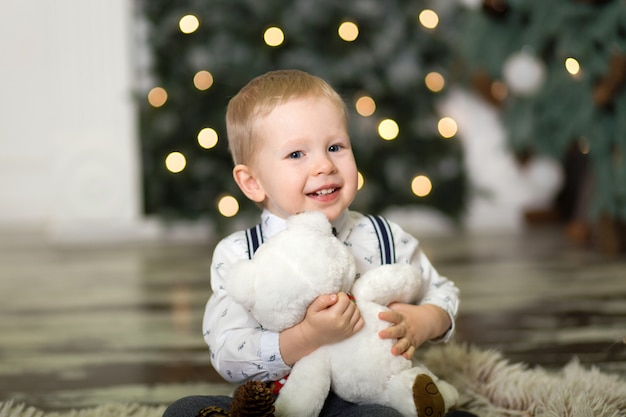 Портрет игры маленького мальчика с плюшевым медвежонком около рождественской елки. рождественские украшения. мальчик радуется своему рождественскому подарку. веселого рождества и счастливого нового года