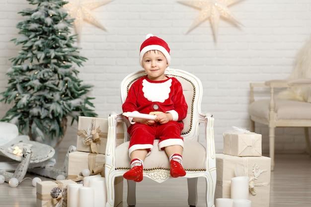 Счастливый маленький улыбающийся мальчик в костюме санта-клауса сидит на кресле возле елки и держит рождественскую подарочную коробку