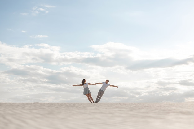 砂の砂漠でお互いの腕を持って踊るロマンチックなカップル